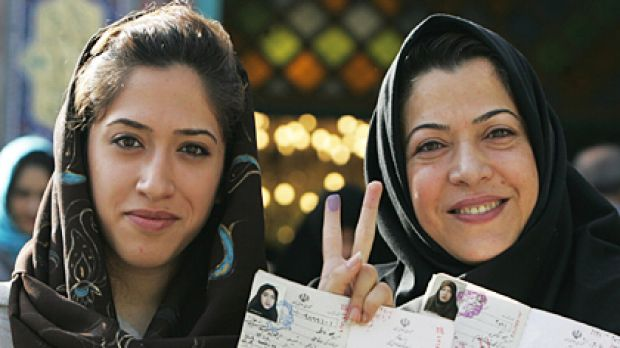 Iranian women show the ink on their fingers and their identification after voting in Tehran yesterday. Women have become ...