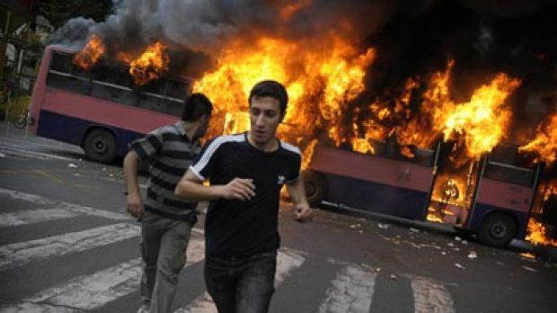Opposition fury ... supporters of the defeated candidate Mir-Hossein Mousavi run past a burning bus on Saturday.