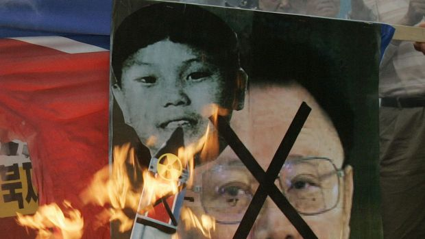 Flashback ... Pictures of North Korean leader Kim Jong-il and his son Kim Jong-un burnt during  anti-North Korea rally ...