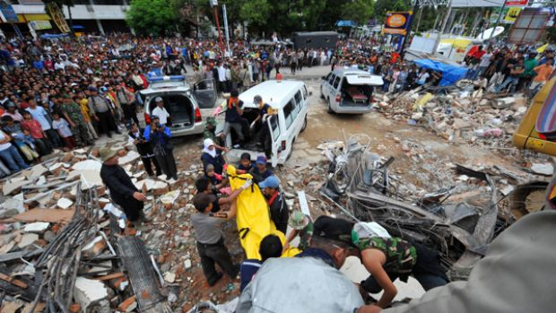 Indonesian rescuers search through the rubble of a colapsed building in Padang.