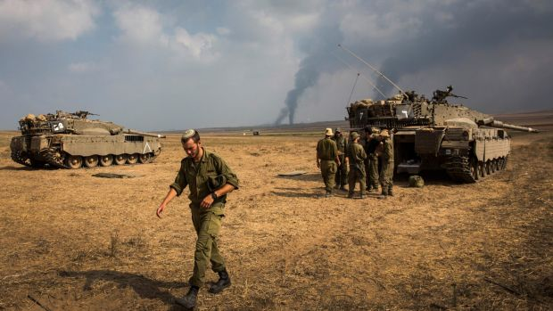 Israeli soldiers stand near their tank while smoke rises from Gaza during Operation Protective Edge in July 2014.