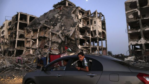 A Palestinian boy in a car drives past destroyed buildings in Beit Lahiya, northern Gaza Strip, in August 2014.