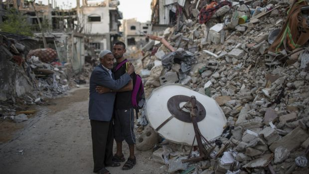 Palestinian Olympian Nader al-Masri and his father beside the rubble of their home in Beit Hanoun in Auust 2014.