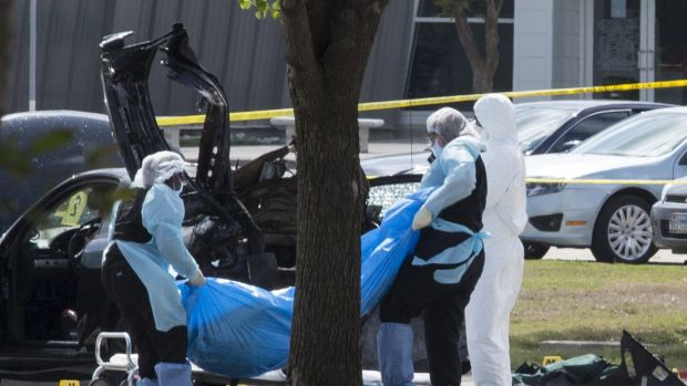 The bodies of gunmen Elton Simpson and Nadir Soofi are removed from behind a car during an investigation by the FBI and ...