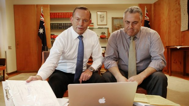 Prime Minister Tony Abbott poses with Treasurer Joe Hockey as they look through the 2015 budget.