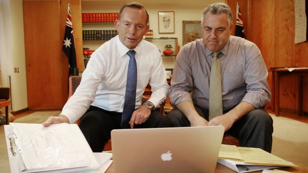 Prime Minister Tony Abbott poses with the Treasurer Joe Hockey as they look through budget papers.