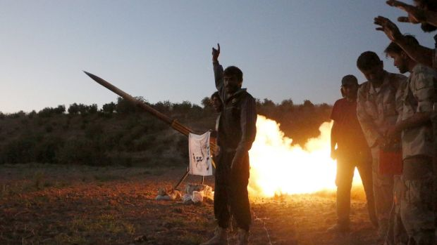 Tajammu Al-Ezza brigade fighters fire a shell towards the forces of Syria's President Bashar al-Assad stationed at ...