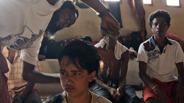 A migrant helps cut his friend's hair at a sports stadium that was turned into a temporary shelter in Lhoksukon, Aceh ...