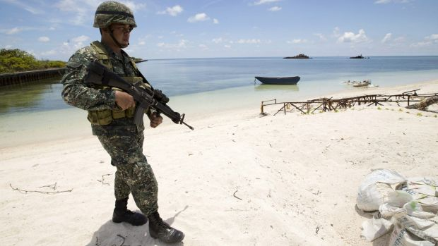 A Filipino soldier patrols the shore of Pag-asa Island in the Spratly chain on Monday.