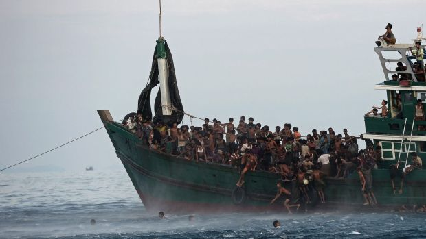 Rohingya migrants jump from their overcrowded vessel after a food drop.