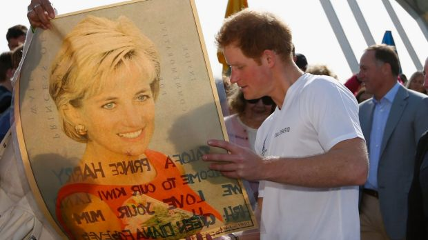 Prince Harry looks at a picture of his late mother Princess Diana from a fan in Auckland, 2015.