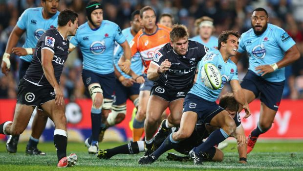 Nick Phipps of the Waratahs gets a pass away against the Sharks on Saturday night.