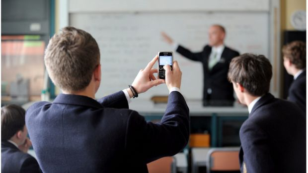 Students at a school in Melbourne use their mobile phones in class.