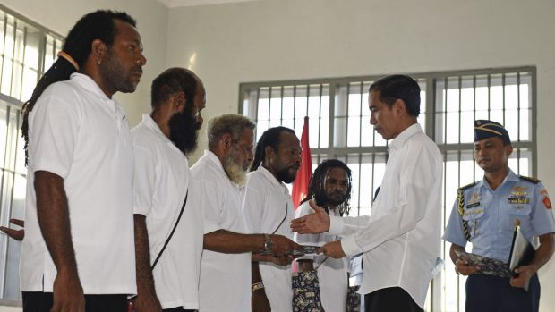 Indonesia's President Joko Widodo (right) hands over official pardons to five Papuan political prisoners belonging to ...