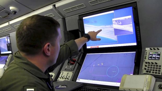A US Navy crewman aboard a P-8A Poseidon surveillance aircraft views a computer screen purportedly showing Chinese ...