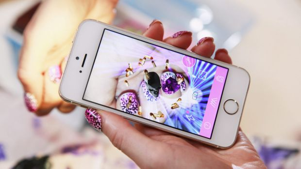 Thea Baumann scans her nail to show the hologram on her phone.