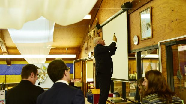 Adrian Piccoli photographs a story on a library wall about David Gonski's visit to Villawood North Public School. The ...