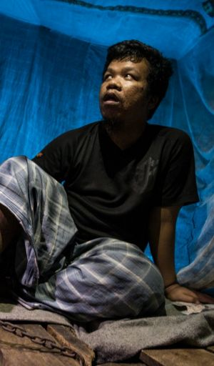 Azman Jantravadi, 27, has been chained by one leg in a corner of his family's barren wooden house.
