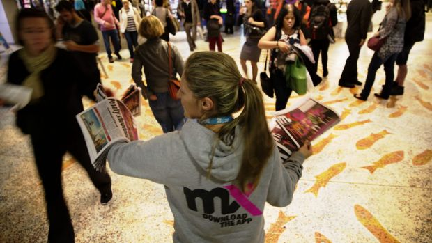 <i>mX</i> newspapers are handed out to commuters at Sydney Town Hall on Thursday.