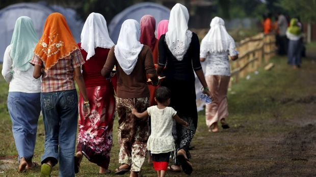 Rohingya migrants who arrived in Indonesia last week by boat walk back after collecting breakfast at a temporary shelter ...