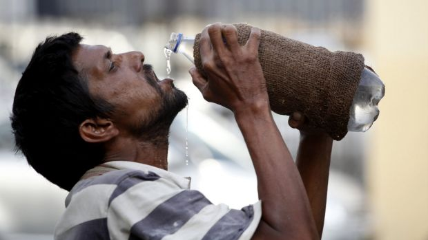 An Indian drinks water from a bottle in Allahabad, India.