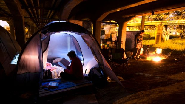 The young homeless woman, 19, studying by her tent in Melbourne.