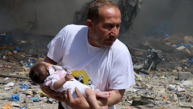 A man holds a baby that survived what activists said was a site in Aleppo hit by a barrel bomb dropped by forces loyal ...