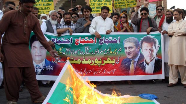 An activist of Pakistan Tehreek e Insaaf party torches a Myanmar flag during a protest in support of Rohingya Muslims in ...