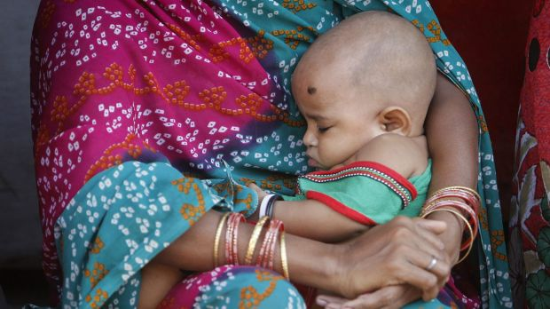A woman holding her baby sits in a street at a slum in Mumbai last year.
