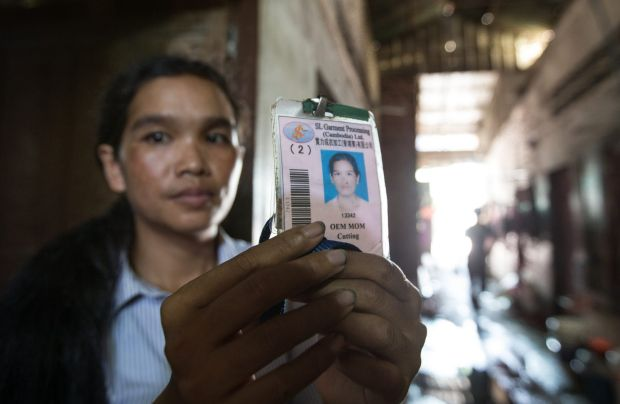 Oem Mom, 33, with her identity card. She works sewing designer jeans for export.  She says her wage is not enough to ...