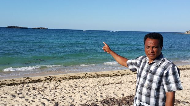 Semuel Messak, the head of Landu village, pointing to the rocks where the boat came ashore.