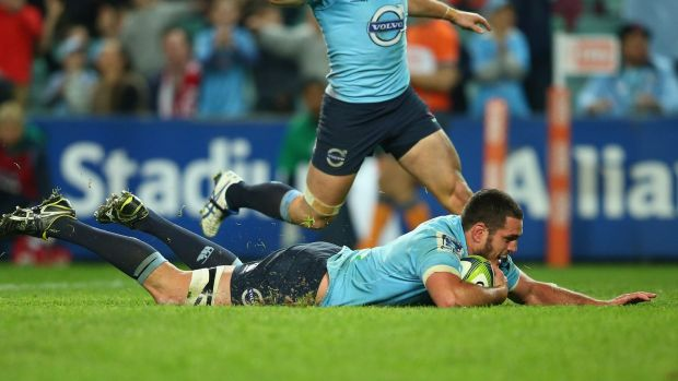 Five points:  David Dennis of the Waratahs dives over to score a try against the Reds.