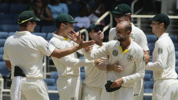 Australia's Nathan Lyon (no cap) is congratulated by his teammates after taking two wickets in consecutive deliveries to ...