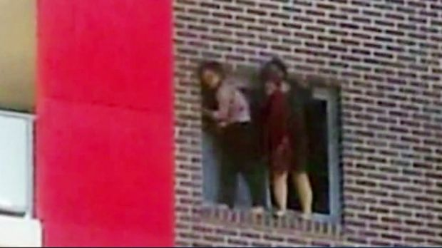 """Ping Kang """"Connie"""" Zhang and Yinuo """"Ginger"""" Jiang hang on to the window of their Bankstown flat before jumping to escape ..."""