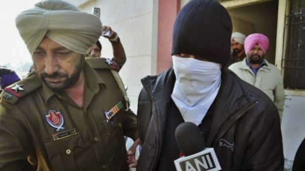 Indian national Puneet Puneet is escorted by police at a district court in India's northern Punjab state in 2013.