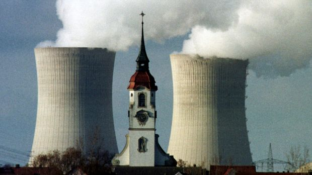 The church spire of the northern Bavarian village of Heidenfeld is dwarfed by the cooling towers of the Grafenrheinfeld ...