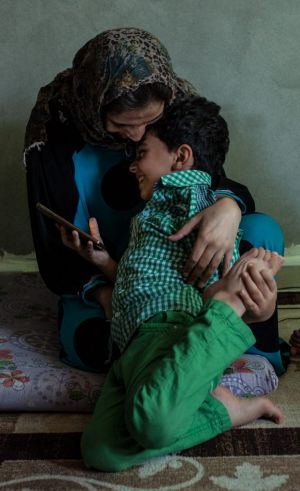 Threats to hold her son Assadullah - seen here in his mother's embrace - forced Basma to flee Tel Abyad in February 2014.