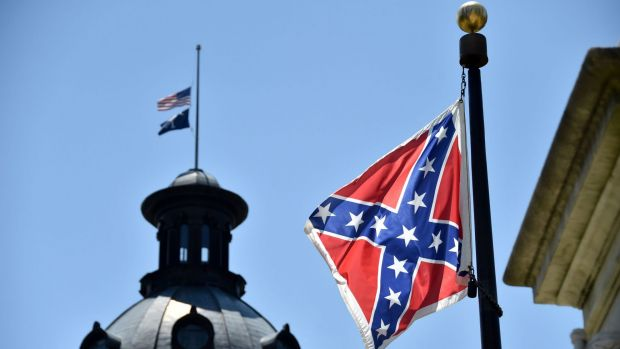 The South Carolina and American flags flying at half-mast behind the Confederate flag at the State Capitol building in ...