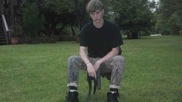 A handout photograph posted to a website with a racist manifesto appears to show Dylann Roof posing with a handgun.