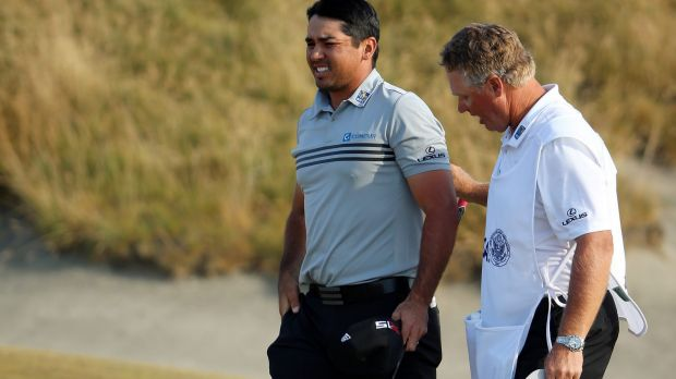 Jason Day of Australia walks off the 18th green with his caddie Colin Swatton after shooting a two-under par 68 during ...