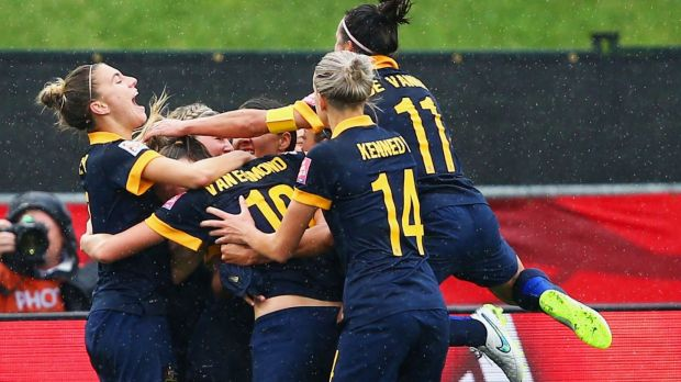 Kyah Simon of Australia (obscured) is mobbed by teammates after scoring the winning goal.