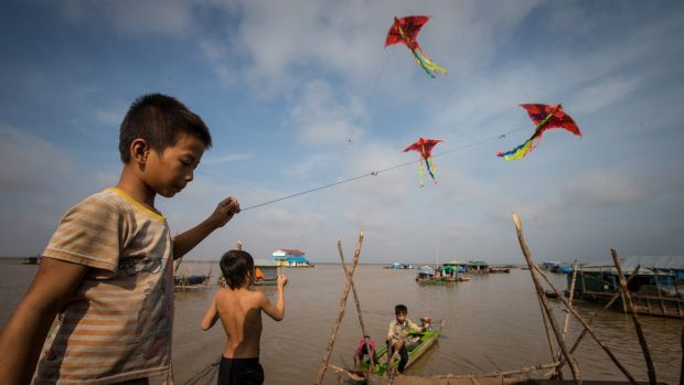 Children fly kites in the floating village.