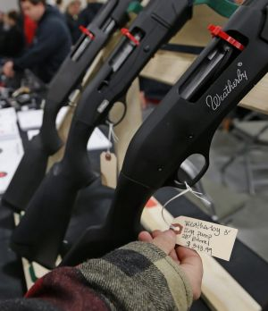 A man looks at the tag of a Weatherly shotgun for sale at a Rocky Mountain Gun Show in Sandy, Utah.