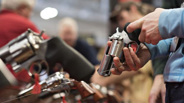 An attendee handles a revolver on the exhibition floor of the 144th NRA Annual Meetings and Exhibits in Nashville, ...