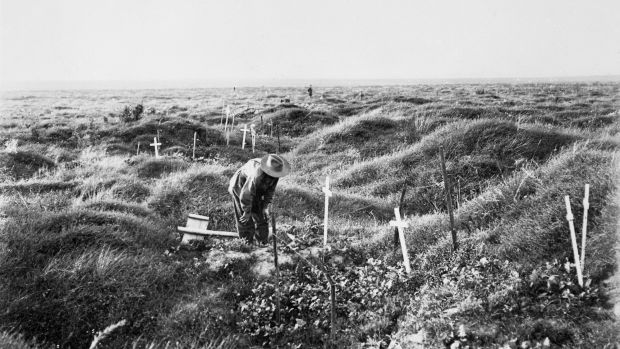 An Anzac soldier scrutinises a grave near Pozieres, along the line of OG1 trench in 1917, the year after the battle for ...