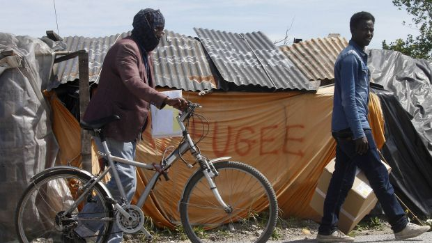"Migrants walk past a shelter at a makeshift camp known as the ""jungle"" in Calais, northern France."