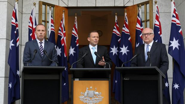 Tony Abbott appears with Peter Dutton and George Brandis in front of 10 flags at a press conference at which he ...