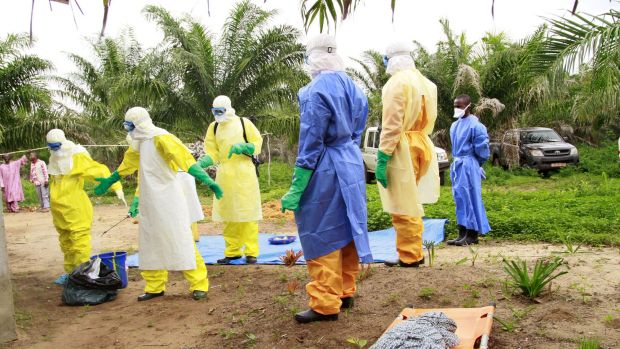 The wrapped remains of a new born child suspected of contracting the Ebola virus, lays on a stretcher as health workers, ...