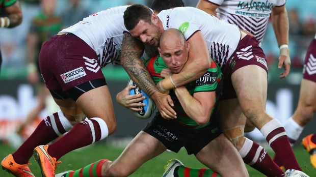 Hard yards: Ben Lowe of the Rabbitohs is swamped by Manly defenders.