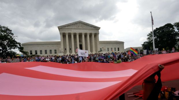 People wave a giant equality flag in celebration outside the Supreme Court in Washington on Friday.